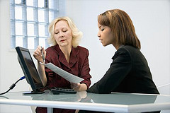 Businesswomen sitting at office desk going over paperwork.